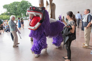 A woman takes a photo of someone dresses like a giant purple Japanese cat. (Photo: National Gallery of Art)