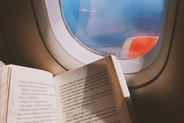 Someone holding a book beside an airplane window through which part of the wing is visible. (Photo: Oleg Magni/Pexels)