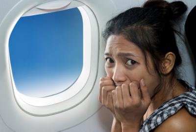 Asian woman sitting beside an airplane window biting her nails. (Photo: Shutterstock)