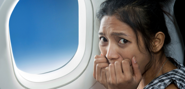 Asian woman sitting beside an airplane window biting her nails. (Photo: Shutterstock)