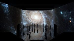 """People visiting """"Infinite Space,"""" which has a projection of outerspace on the walls. (Photo: Artechouse)"""