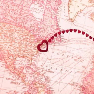 Pink map showing Atlantic Ocean with line made from hearts from Great Britain to the US. (Photo: PeskyMonkey/Getty Images)