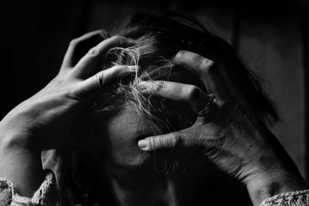 Black and white photo of woman holding her head in her hands. (Photo: Kat Jane/Pexels)