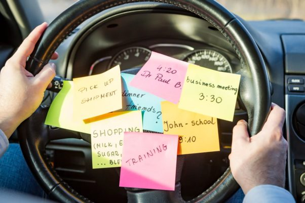 Sticky notes with different reminders stuck on the middle of a steering wheel. (Photo: Shutterstock)