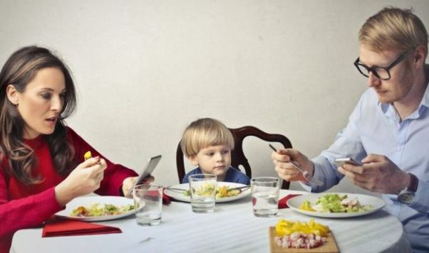 A mother and father use their smart phones at the dinner table while their toddler son looks on. (Photo: Getty Images)