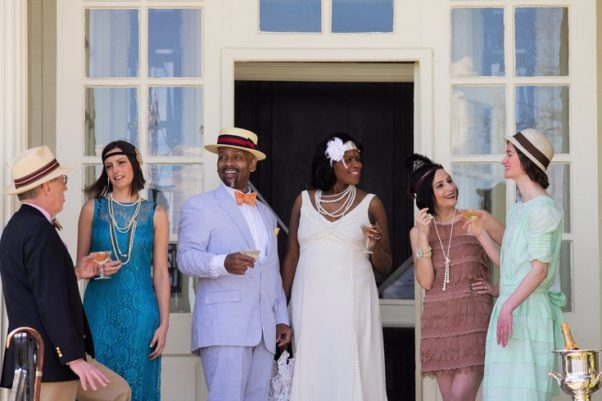 Partygoers dressed in 1920s fashions drinking cocktails. (Photo: Annie Vickery Photography)