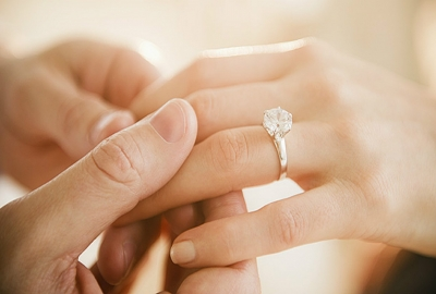 A man's hand holding a woman's hand with an engagement ring on it. (Photo: Getty Images)