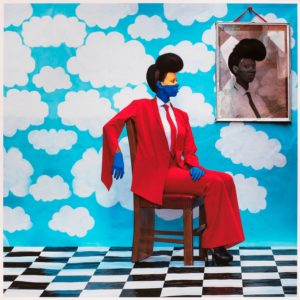 """""""Sai Mado (The Distant Gase)""""is a composit photo of an African woman dressed in a man's red suit and tie sitting on a chair with drawn clouds in a blue sky behind her. (Photo: Aida Muluneh)"""