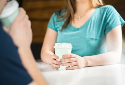 Two women at a coffee shop drinking coffee out of paper cups. (Photo: Getty Images)