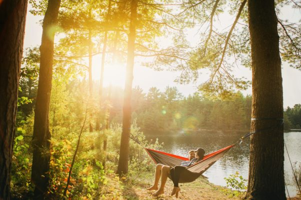 Man sitting in a hammock byseide a lake. (Photo: Esther Tuttle/Unsplash)