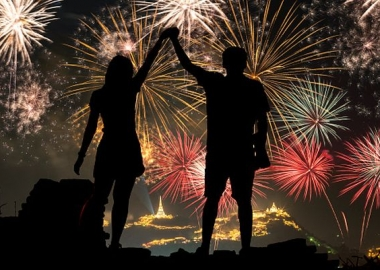 Sillouette of two people holding hands with fireworks in the background. (Photo: Dreamstime)
