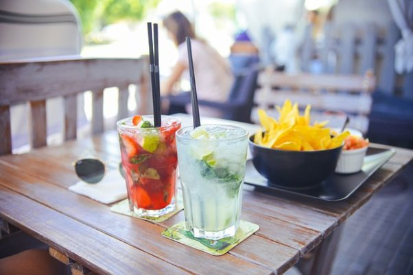 Outdoor table with drinks and nachos sitting on it with people in the background. (Photo: Stokpic/Pixabay)