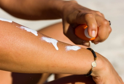 Person squirting suncreen on their arm. (Photo: Getty Images)
