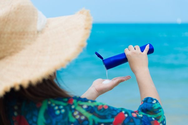 Woman weaing a hat and shirt on the beach pouring sunscreen into her hand. (Photo: iStock Photo)
