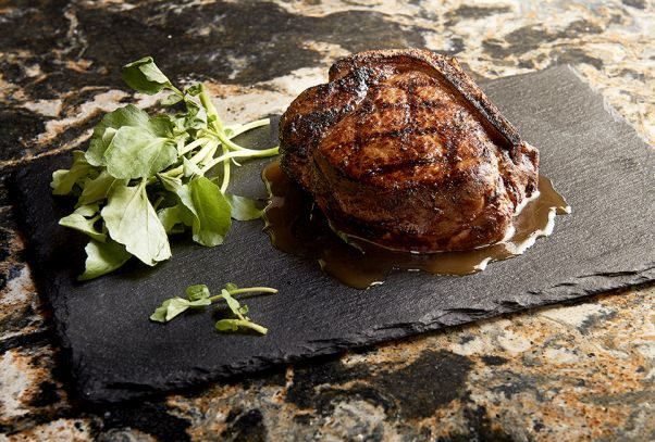 Bone-in filet mignon on a slate with some garnish beside it. (Photo: Morton's)