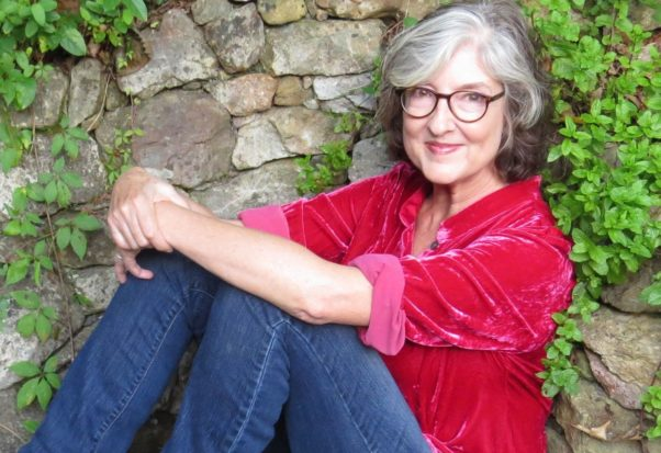 Barbara Kingsolver sittng on the ground in a red shirt and jeans. (Photo: Steven Hopp)