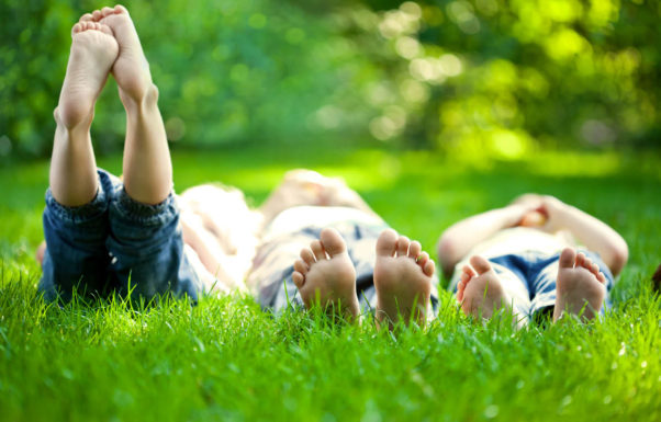 Three young people lay side by side in a grassy area. The photo is taken from the ground, viewing their feet. The person on the left has their feet raised into the air. A line of trees is in the background, out of focus. (Photo: Getty Images)