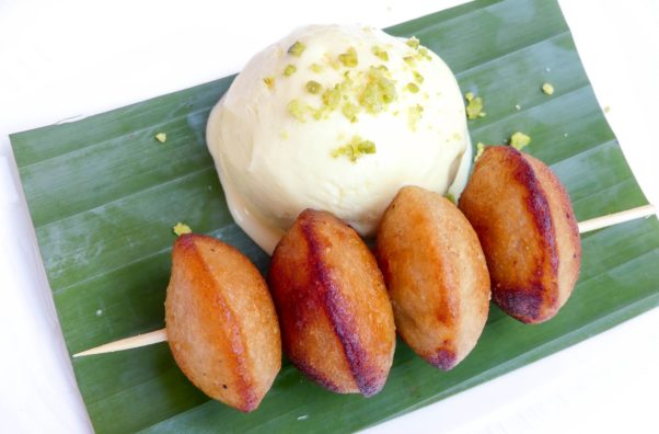 Four sweet kushi paniyaram on a skewer on a plate with a bowl of ice cream. (Photo: Raisika)
