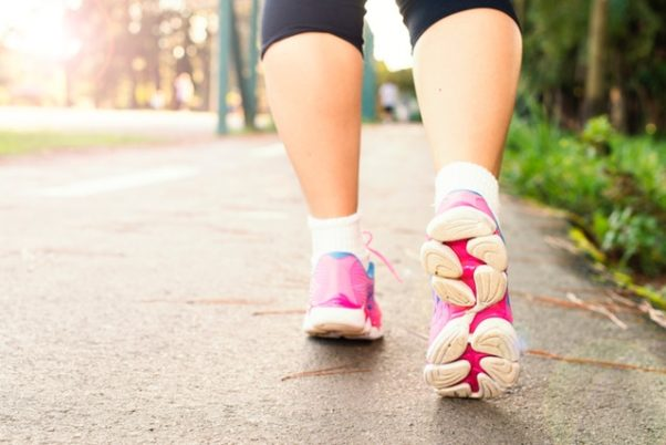 A woman's feet in pink sneakers running away from the camera. (Photo: Daniel Reche/Pexels)