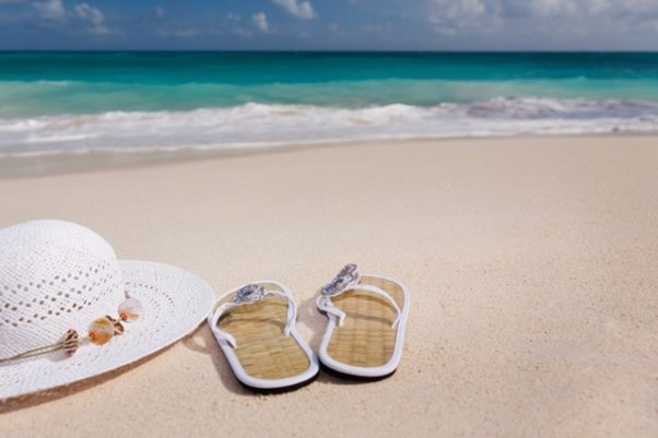 A pair of white flip-flops and a wide-brimmed woman's hat sitting on the sand beside the water. (Photo: Public Domain Pictures/Pexels)