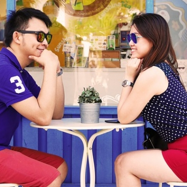 Asian couple sitting across the table from each other at an outdoor cafe. (Photo: Pexels)