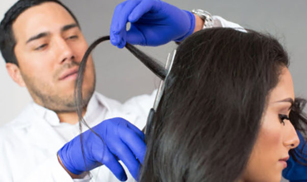 Male lab technician cutting a strand of a woman's hair for a drug test. (Photo: Employer Solutions)