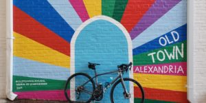 A bicycle sitting in front of a mural of a blue dorway with rainbow colors radiating out of it. (Photo: Alexandria Bicycle and Pedestrian Advisory Committee)