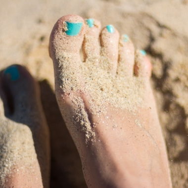 Woman's feet in the sand with her toenails painted a shade of aqua. (Photo: Juja Han/Unsplash)