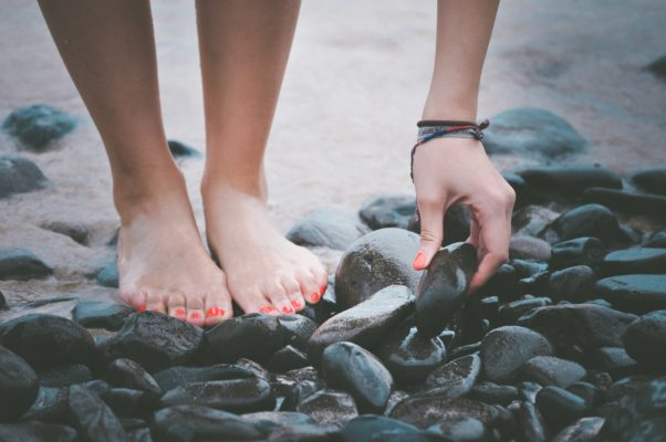 A woman's feet standing on rocks in the water with her nails painted bright orange. (Photo: Priscilla du Preez/Unsplash)