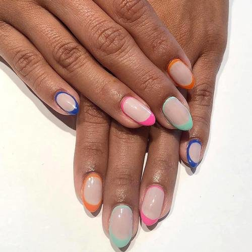 Woman's hands with almondl shaped nails tipped in different pastel colors. (Photo: Olivia & June)