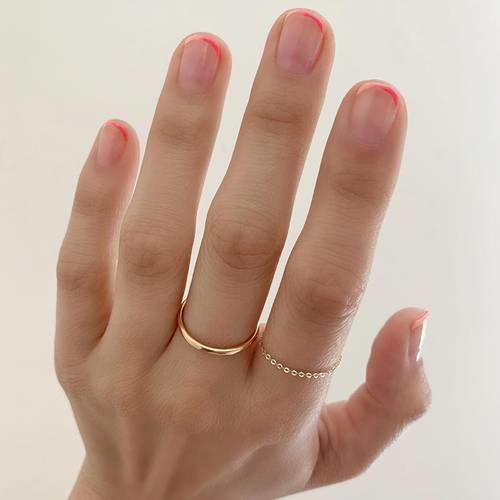 Woman's hand with a thin French manicure in neon pink. (Photo: Betina Goldstein)