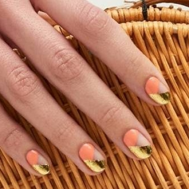 Woman's hand with peach beds and gold tips. (Photo: Paintbox)