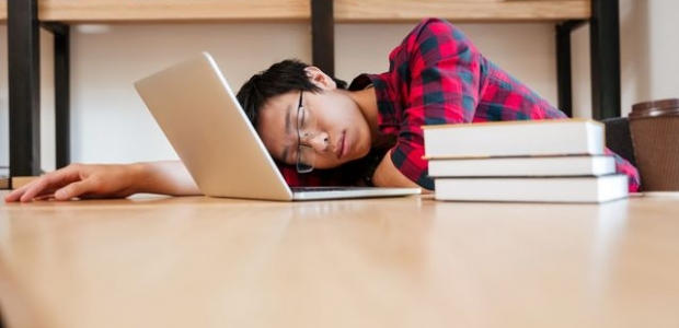 An Asian boy sleeping in the library with his laptop open on a table beside a pile of books. (Photo: Footage Firm Inc.)
