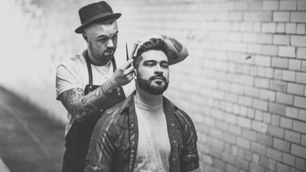 Black and white photo of a bearded manb getting a haircut from a tattooed man wearing a hat. (Photo: Thom Holmes/Unsplash)
