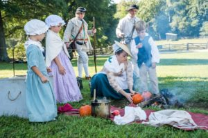 A family dressed in Colonial garb roasts pumpkins over an open fire. (Photo: Mount Vernon)