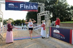 A woman crossing the finish line with the ribbon held by woman in colonial garb. (Photo: Mount Vernon)