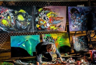 A man paining a picture with several pictures diplayed behind him. (Photo: Art All Night)