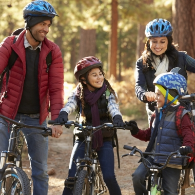 Two Hispanic parents with their son and daughter on bikes in a park on a path in the woods. (Photo: Getty Images)