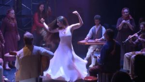 A woman salsa dancing in the center of musicians. (Photo: Theatre J)