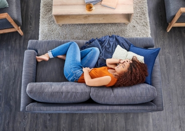 Woman lying on a couch holding her stomach in pain. (Photo: Getty Images)