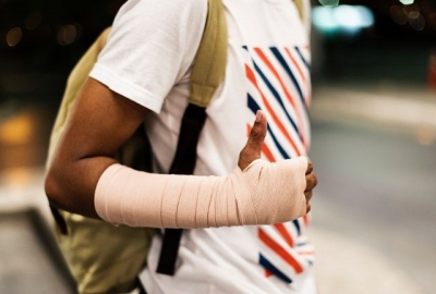 African American man with his arm in a cast carrying a backpack. (Photo: Raw Pixels/Pexels)