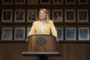 Heidi Schreck wearing a gold blazer standing behind a podium with the American Legion emblem on it. (Photo: Johan Persson)