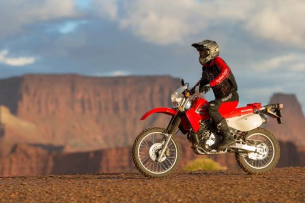 A man riding a red Honda XR650L motorcycle on top of a plateau. (Photo: Americna Honda Motor Co.)