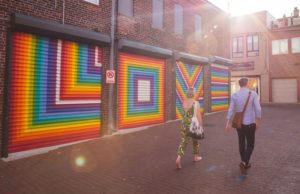"""A man and woman walk past the word """"Love"""" painted in rainbow letters on garage doors in Blagden Alley. (Photo: Destination D.C.)"""
