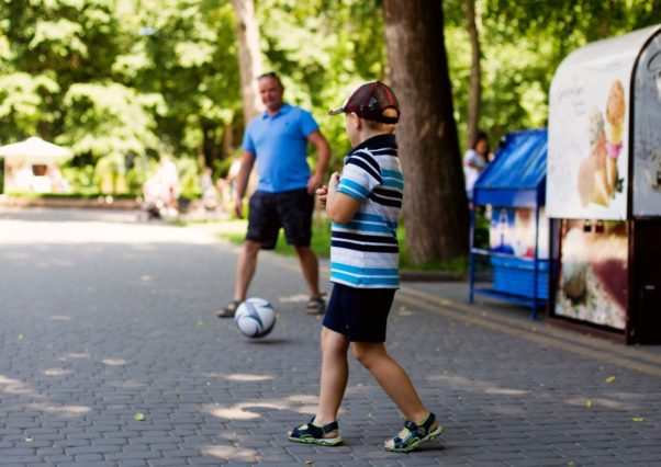 Father and son playing soccer outside. (Photo: Mariana Kurnyk/Pexels)
