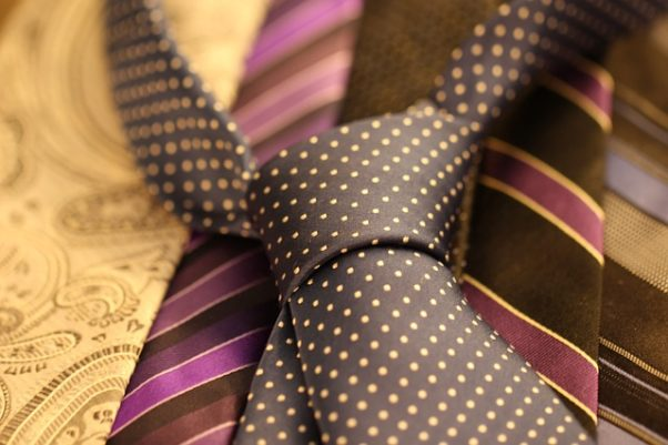 A knotted brown polka dot tie laying on top of other striped ties. (Photo: Mira Cosic/Pixabay)