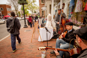 Musicians play on the sidewalk in Book Hill as shoppers walk by. (Photo: Sam Kittner/Georgetown BID)