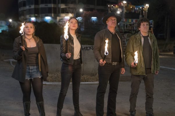 Little Rock (Abigail Breslin), Wichita (Emma Stone), Tallahassee (Woody Harrelson) and Columbus (Jesse Eisenberg) standing outside holding flaming sticks. (Photo: Sony Pictures)