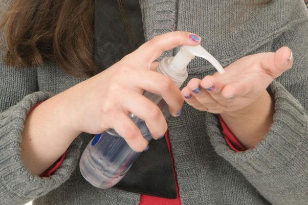 Young girl holding a bottle of hand sanitizer and squirting some onto her left hand. (Photo: iStock)