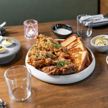 Ranch friend chicken in a bowl with Texas toast on a table. Plates of deviled eggs, pickles, and sauces surround it. (Photo: Anne Kim)